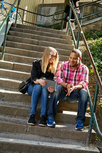 Sweden, Man and woman sitting side by side on steps and looking at digital tabletの写真素材 [FYI02206938]