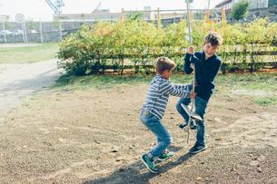 Sweden, Blekinge, Karlskrona, Boys (8-9) playing with rope swingの写真素材 [FYI02206956]