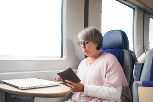 Sweden, Senior woman sitting on train and using phoneの写真素材 [FYI02206972]