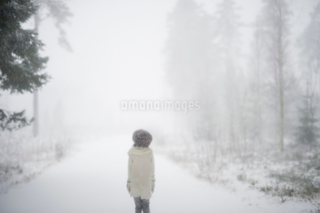 Sweden, Vastmanland, Bergslagen, Girl (8-9) in winter forestの写真素材 [FYI02207028]