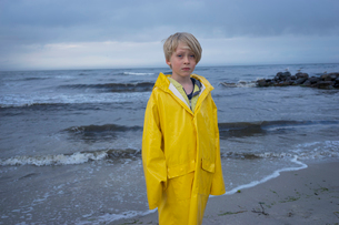 A young boy at the beach in wet weather gearの写真素材 [FYI02207041]