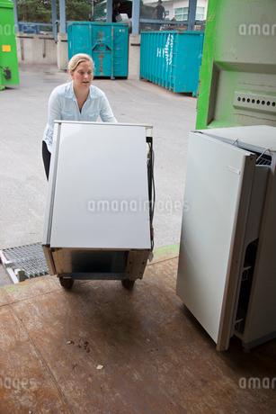 Finland, Uusimaa, Woman loading refrigerator into truckの写真素材 [FYI02207045]