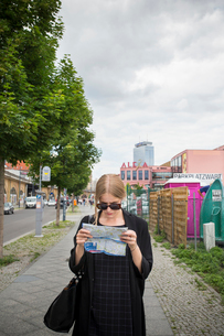 Germany, Berlin, Young woman with city mapの写真素材 [FYI02207072]