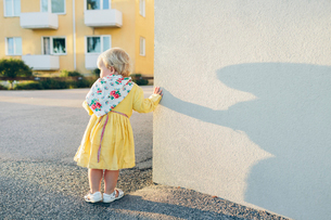 Sweden, Blekinge, Karlskrona, Girl (2-3) leaning against wallの写真素材 [FYI02207145]