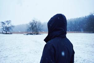 A man in a black jacket standing in a snowy fieldの写真素材 [FYI02207165]