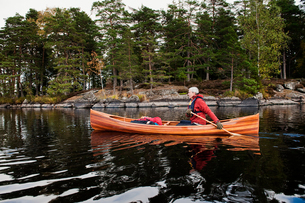 Sweden, Smaland, Mature man in boat on lake with forest on shoreの写真素材 [FYI02207187]