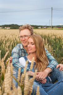 Finland, Uusimaa, Siuntio, Mid adult couple sitting in wheat fieldの写真素材 [FYI02207188]