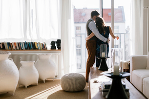 Germany, Couple hugging by window in living roomの写真素材 [FYI02207202]
