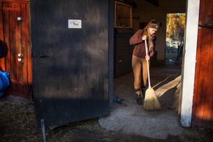 Sweden, Uppland, Faringso, Woman sweeping in barnの写真素材 [FYI02207218]