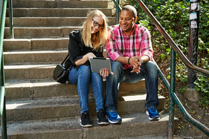 Sweden, Man and woman sitting side by side on steps and looking at digital tabletの写真素材 [FYI02207232]