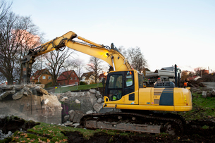 Sweden, Vastra Gotaland, Bulldozer by ruined building in streetの写真素材 [FYI02207283]