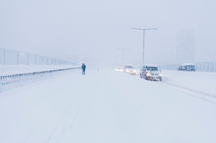 Cars and a pedestrian during snow in Stockholmの写真素材 [FYI02207284]