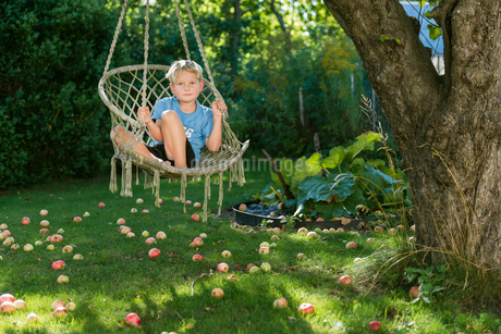 Sweden, Sodermanland, Nacka, Boy (6-7) sitting in chair hammockの写真素材 [FYI02207287]