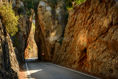 Spain, Mallorca, Empty road between tall rocksの写真素材 [FYI02207293]