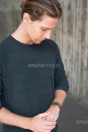 Sweden, Skane, Malmo, Portrait of blonde man checking time on wristwatchの写真素材 [FYI02207295]