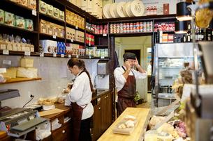 Sweden, Woman working, man talking on phone in food storeの写真素材 [FYI02207320]
