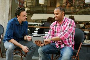 Sweden, Mature men looking at digital tablet in sidewalk cafeの写真素材 [FYI02207335]