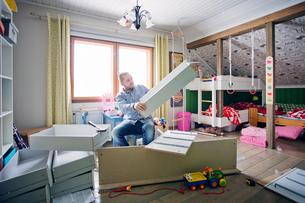 Finland, Man building cabinet in nurseryの写真素材 [FYI02207342]