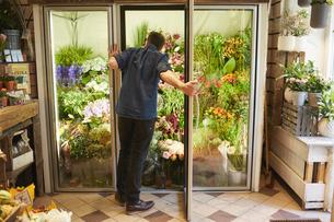 Sweden, Florist opening door in flower shopの写真素材 [FYI02207350]