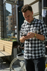 Sweden, Stockholm, Man texting outdoorsの写真素材 [FYI02207352]
