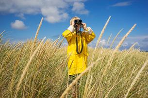 A young boy in wet weather gear looking through binocularsの写真素材 [FYI02207356]
