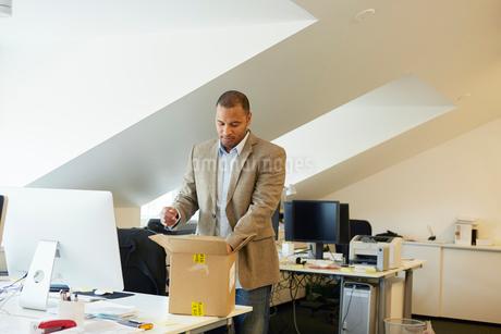 Sweden, Businessman opening package in officeの写真素材 [FYI02207368]