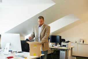 Sweden, Businessman opening package in officeの写真素材 [FYI02207368]