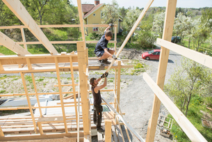 Sweden, Sodermanland, Mid adult men constructing wooden buildingの写真素材 [FYI02207384]