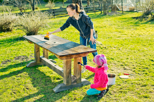 Finland, Paijat-Hame, Heinola, Mother with daughter (4-5) oiling wooden table in gardenの写真素材 [FYI02207385]