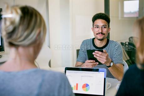 Sweden, Professionals talking at deskの写真素材 [FYI02207390]