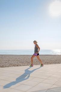 Spain, Altea, Woman exercising at beach by Mediterranean Seaの写真素材 [FYI02207421]