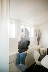 Woman on the phone behind a windowの写真素材 [FYI02207434]