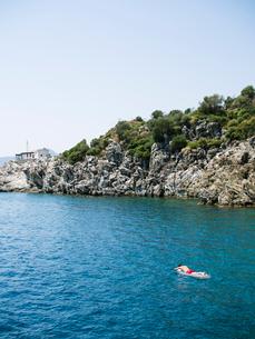 Turkey, Mugla, Marmaris, Man floating on mattress by rocky coastの写真素材 [FYI02207449]