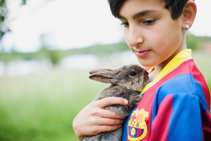 Sweden, Varmland, Filipstad, Gasborn, Horrsjon, Boy (10-11) in sport jersey holding rabbitの写真素材 [FYI02207450]