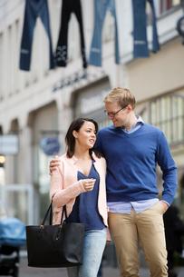 Sweden, Vastergotland, Gothenburg, Young couple walking and hugging in streetの写真素材 [FYI02207451]