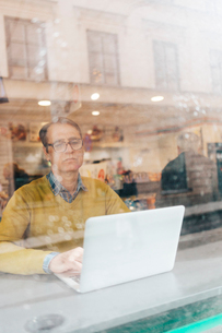 Man using a laptop behind a windowの写真素材 [FYI02207455]
