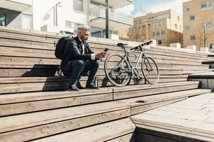 Man on staircase with bicycle in Sodermanland, Swedenの写真素材 [FYI02207459]
