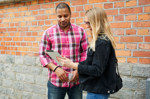 Sweden, Man and woman looking on digital tablet against brick wallの写真素材 [FYI02207461]