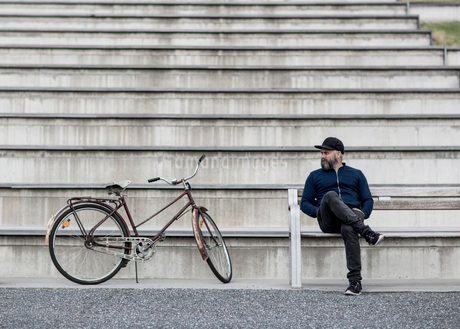 Man with bicycle sitting on staircase in Vasterbotten, Swedenの写真素材 [FYI02207487]