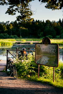 Sweden, Uppland, Stockholm, Djurgarden, Cyclist resting near information plate by pond in parkの写真素材 [FYI02207513]