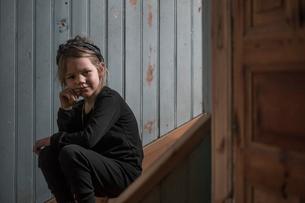 Sweden, Portrait of blonde girl (4-5) sitting on wooden stepsの写真素材 [FYI02207535]