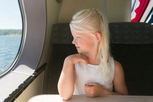 Sweden, Girl (6-7) looking through window on shipの写真素材 [FYI02207552]