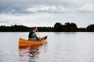 Sweden, Smaland, Mature man in boat on lake with forest on horizonの写真素材 [FYI02207559]