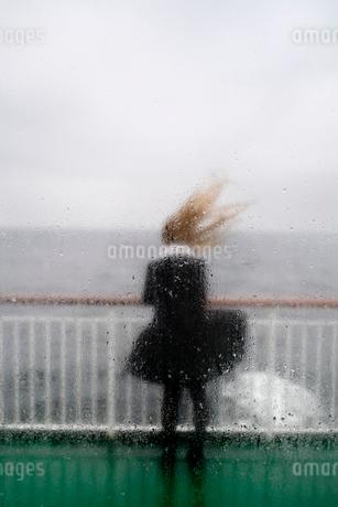 Sweden, Rear view of young woman behind wet windowの写真素材 [FYI02207597]