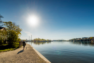 Sweden, Stockholm, Skeppsholmen, Woman walking with dog near harborの写真素材 [FYI02207607]