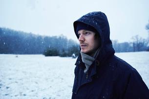 A man in a black jacket standing in a snowy fieldの写真素材 [FYI02207608]