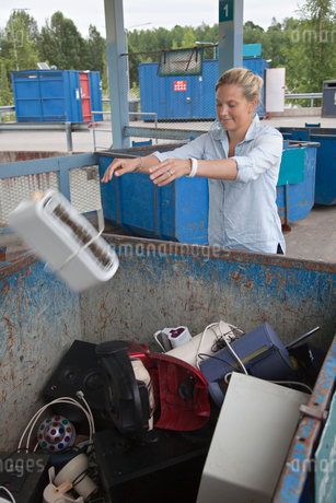 Finland, Uusimaa, Woman throwing old toaster into containerの写真素材 [FYI02207623]