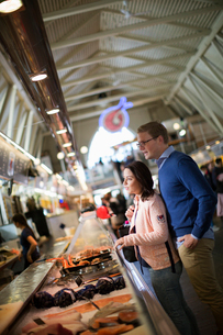 Sweden, Vastergotland, Gothenburg, Young couple buying seafood at marketの写真素材 [FYI02207643]