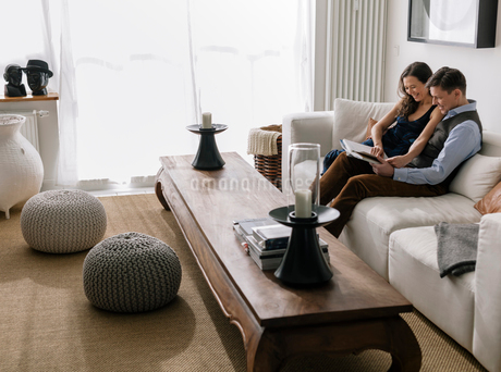Germany, Couple sitting on sofa in living roomの写真素材 [FYI02207711]