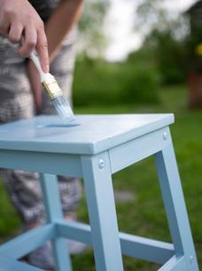 Finland, Ostrobothnia, Woman painting chairの写真素材 [FYI02207714]